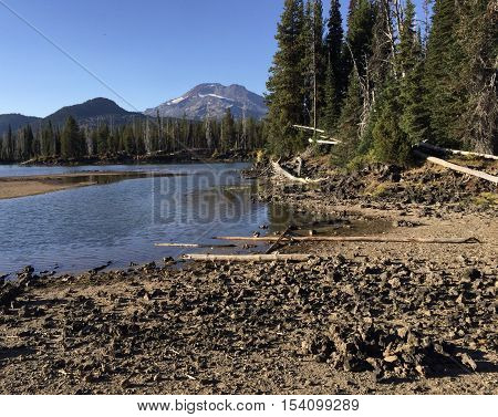 The roccky shore of Sparks Lake in Oregon's Cascade Mountains with the South Sister in the background on a sunny fall day.