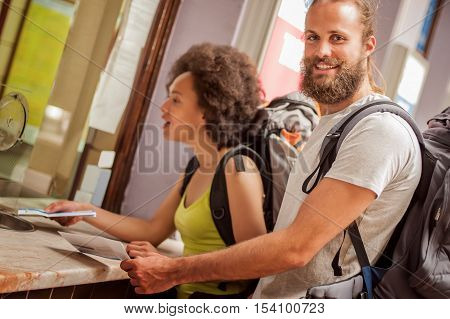 Happy Couple Of Tourists Buy Tickets At Terminal Station Counter