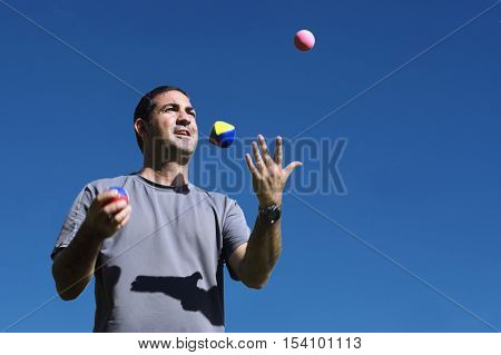 Young man juggler is juggling balls with a blue sky background.