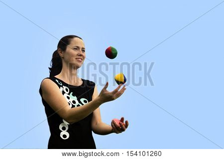 Young woman juggler is juggling balls with blue sky background. poster