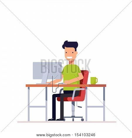 A young employee working at the computer. Programmer or freelancer working at the workplace. Happy young man uses the computer. Monitor and coffee on your table