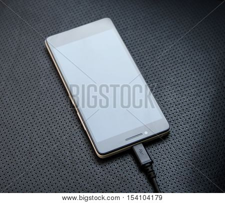 Mobile phone recharging by power cable adapter close up stock photo