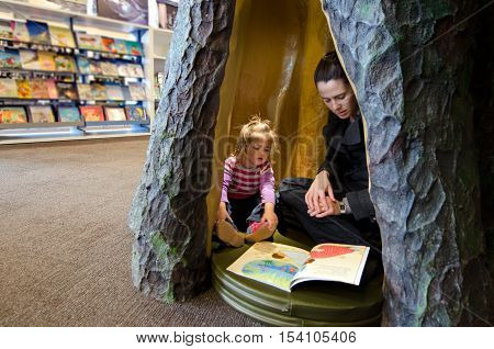 Young Mother Reads A Book To Her Child