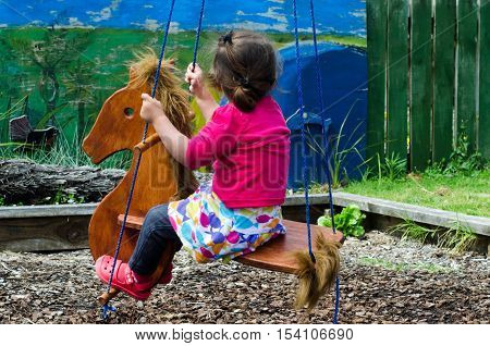 Little Girl Rides On A Toy Horse