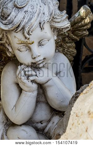 Vertical photo in color of a stoned Cherub from a graveyard