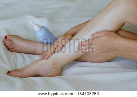 Young Woman Moisturisers Her Legs On White Background
