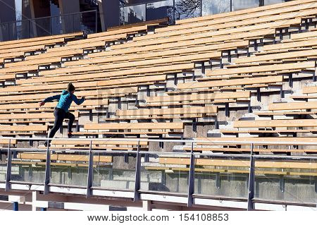 Exercise in stadium. Young woman running stadium stairs.