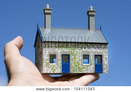 Man's hand holds a toy house against blue sky. Concept photo of Real estate market bubble booming