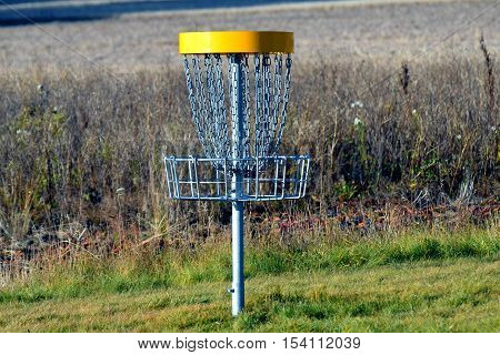 Disc golf target on disc golf course.