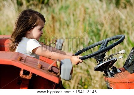 A Little girl drives an old tractor.