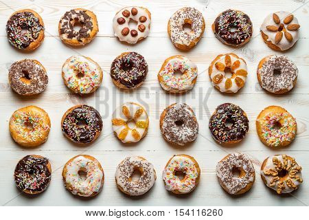 Large group of colorfully decorated donuts on old wooden table
