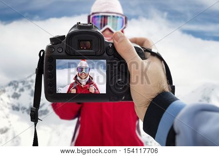 Photographer photographing happy woman on snowy winter day on mountain