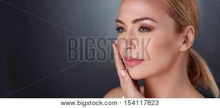 beautiful middle aged female touching her face skin and feel the softness