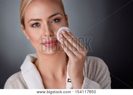 middle aged woman cleaning her skin, health and beauty