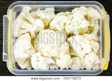 Tray with raw cauliflower for freezing. Stocking up vegetables for winter storage in plastic container