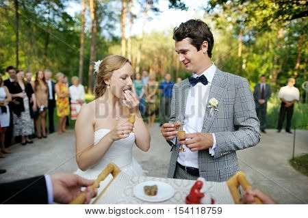 Bride and groom being met by parents with bread and water