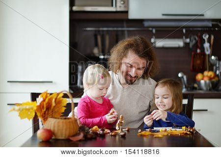 Father and his kids making chestnuts creatures together