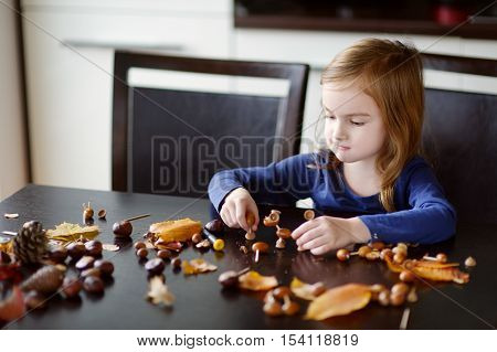 Adorable little girl making chestnuts creatures at home