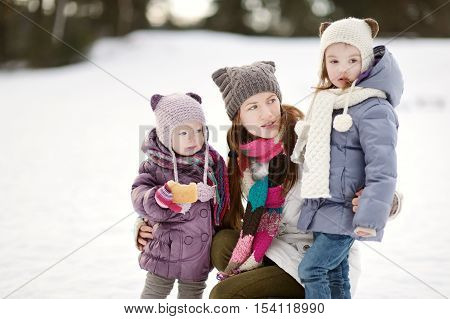 Young Mother And Her Girls On Winter Day