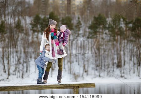 Young Mother And Her Daughters At Winter Day