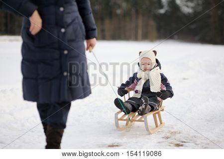 Little Girl Having Sleight Ride On Winter Day
