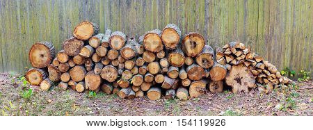 firewood near the fence Stack of birch firewood near the fence