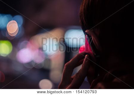 Young man talking on mobile phone at night in front of blurred city lights