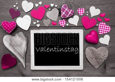 Chalkboard With German Text Valentinstag Mean Valentines Day. Many Pink Textile Hearts. Grey Wooden Background With Vintage, Rustic Or Retro Style. Black And White Style With Colored Hot Spots
