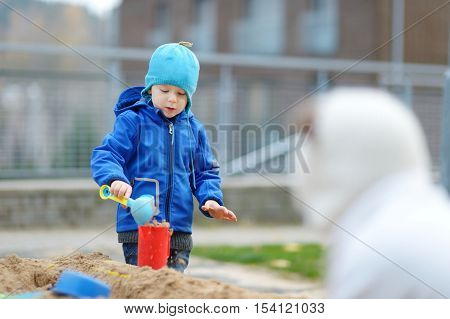 Two kids playing in a sandbox on autumn day