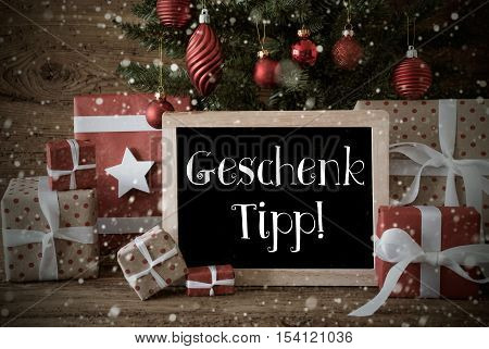 Chalkboard With German Text Geschenk Tipp Means Gift Tip. Nostalgic Card For Seasons Greetings. Christmas Tree With Balls And Snowflakes. Gifts In The Front Of Wooden Background.