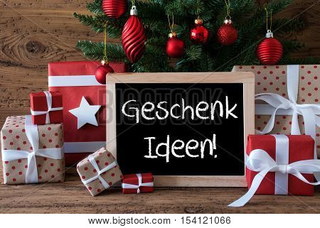 Chalkboard With German Geschenk Ideen Gute Means Gift Ideas. Colorful Christmas Card For Seasons Greetings. Christmas Tree With Red Balls. Gifts Or Presents In The Front Of Wooden Background.