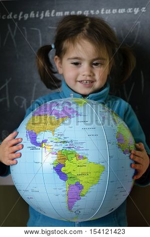 Portrait of a girl holds a globe during geography class. concept photo