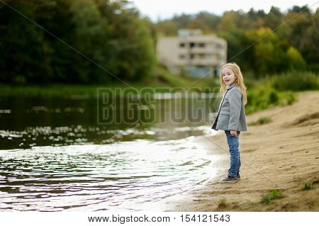 Adorable Little Gilr By A River At Autumn