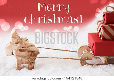 Moose Is Drawing A Sled With Red Gifts Or Presents In Snow. Christmas Card For Seasons Greetings. Red Christmassy Background With Bokeh Effect. English Text Merry Christmas