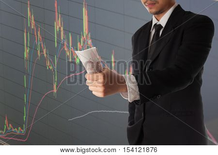 Businessman hand holding money and stock market graph and bar chart price display,Businessman failure in stock market