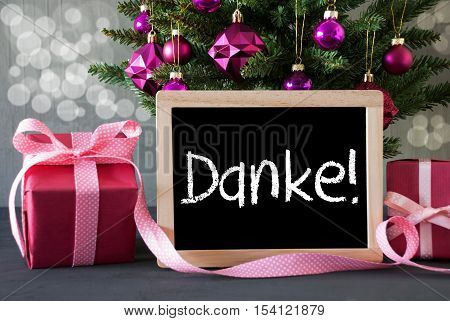 Chalkboard With German Text Danke Means Thank You. Christmas Tree With Rose Quartz Balls And Bokeh Effect. Gifts Or Presents In The Front Of Cement Background.