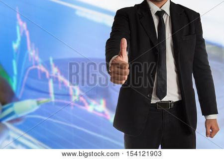 businessman with thumbs up gesture with stock graph,concept of success in stock market