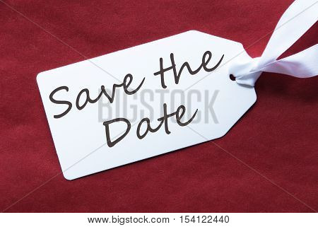 English Text Save The Date. One White Label On A Red Textured Background. Tag With Ribbon.