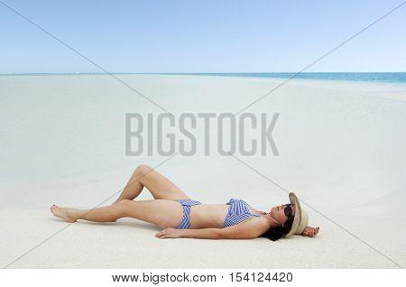Young Woman Sunbathing On Aitutaki Lagoon Cook Islands