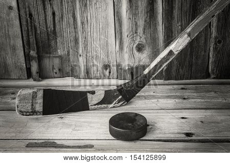 horizontal sepia image of an old vintage hockey stick with an old puck on a rustic old wood board background.