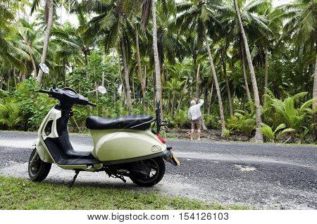 AITUTAKI - SEP 20:Tourist man explore the nature with motorbike on Sep 20 2013.It's one of the must popular activity in the Island but Cook Islands Driver's License is required for motorized rental.