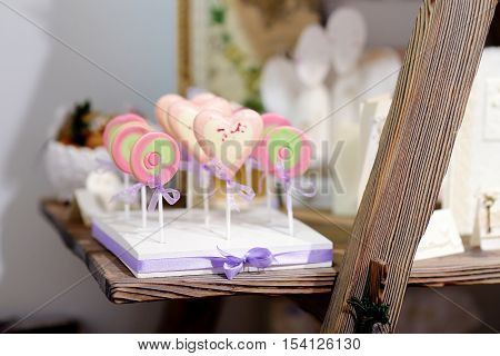 Delicious colorful lollipops on sticks on a table