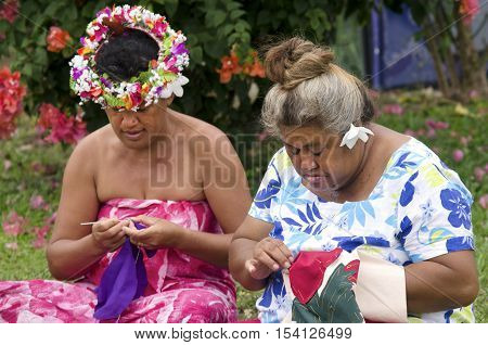Portrait of Polynesian Pacific Island Tahitian mature females sewing Tivaivai outside their home in Aitutaki lagoon Cook Islands.