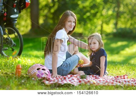 Young Mother And Her Daughter Having A Picnic