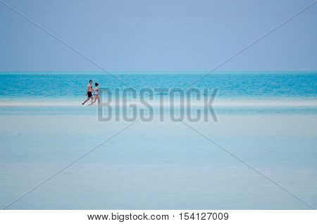 Young couple male and female walks on the white sand of Aitutaki Lagoon Cook Islands