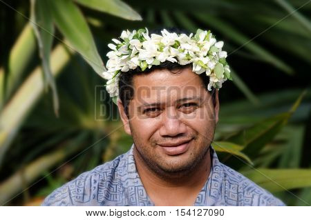 Portrait of Polynesian Pacific Island Tahitian mature male wearing exotic flowers top bouquet smile out side his home garden in Aitutaki lagoon Cook Islands.