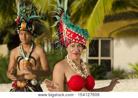 Portrait of attractive young Polynesian Pacific Island Tahitian male and female dancers in colorful costumes dancing on tropical beach during sunset with palm trees in the background.