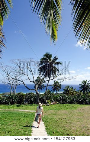 Tourist woman walks on a walking path in a park in Rarotonga Cook Islands.