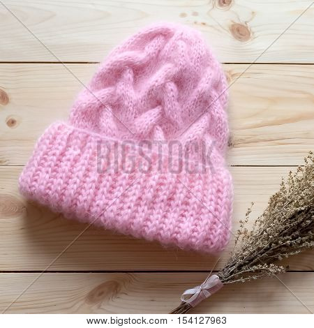 Bound Hand On The Spokes Of Pink Mohair Cap On A Wooden Background With A Bunch Of Dry Grass