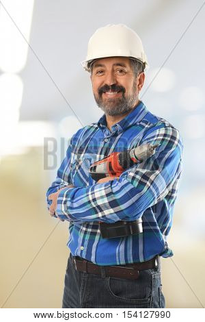 Mature Hispanic builder inside a building with background out of focus